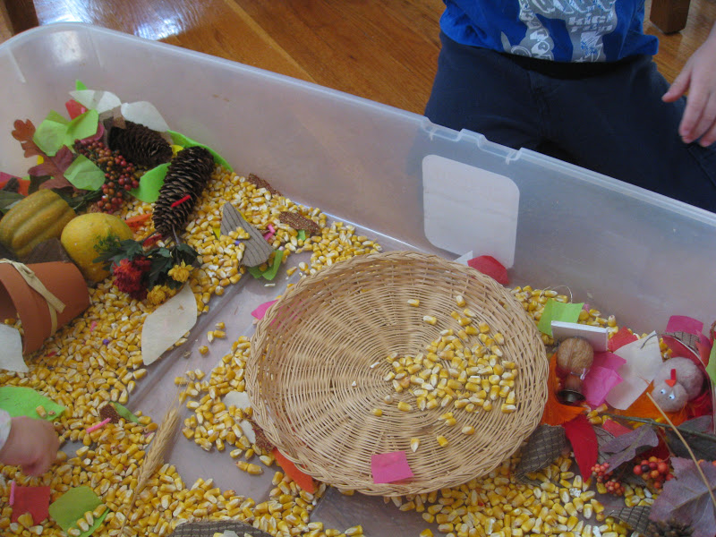 Use baskets, cups, and scoops to help kids build fine motor skills in a Thanksgiving sensory bin.