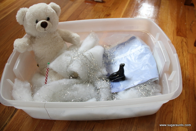 Make a polar bear sensory bin with figures, and sensory materials.