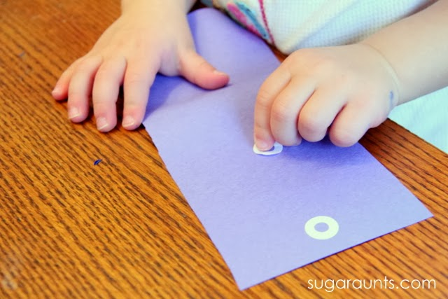 Pincer grasp development by peeling and placing small stickers.