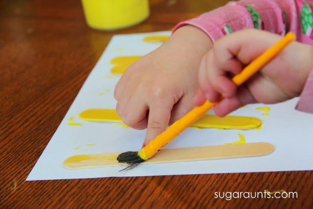 Painting crafting sticks is a great fine motor activity for toddlers.
