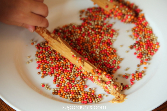 Kids can roll the pretzel rods in sprinkles to make these pretzel rod turkeys.