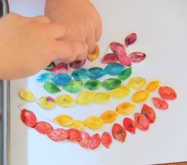 Use colored pumpkin seeds to make a fine motor craft with kids.