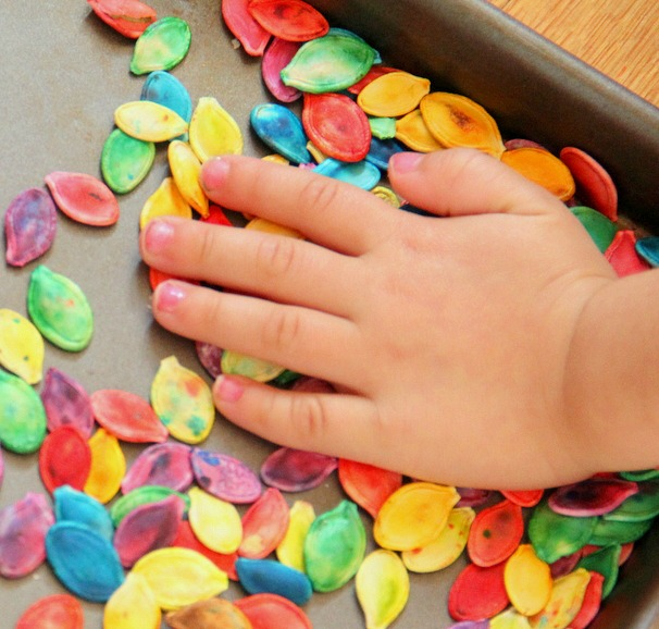 Use dyed pumpkin seeds for sensory play with kids.