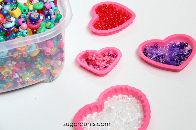 Use heart shaped cookie cutters and beads to work on fine motor skills.