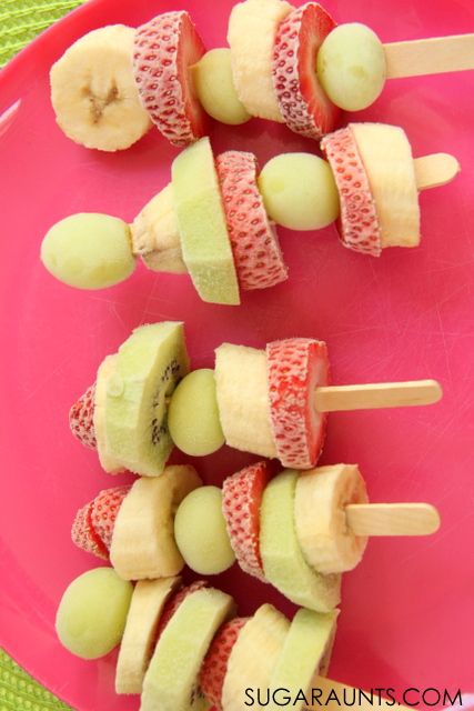 Frozen Fruit Kabob treat.  Kids love to make and eat these frozen treats! So much healthier than sugary popsicles. Perfect for summer snacks and cooking with kids!