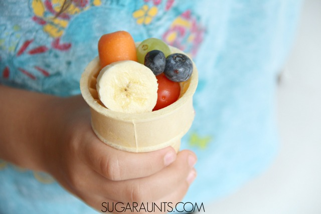 Color snack with colorful fruits and vegetables in an ice cream cone