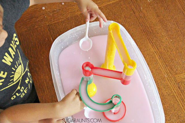 Ooobleck recipe and sensory play with a marble run! This is awesome sensory play and creative fine motor work when kids scoop and pour the oobleck into the marble run.  Watching the oobleck slowly run down the marble run is so mesmerizing and calming!