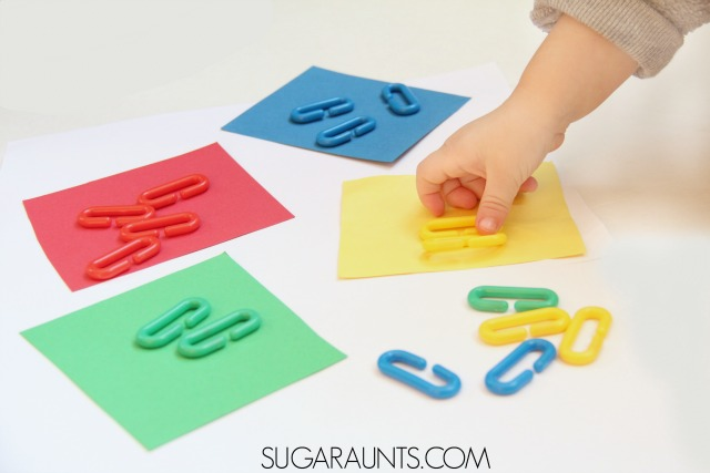 Color sorting activity for toddlers using rainbow plastic chain links for learning and fine motor skills. This is an Occupational Therapists recommended tool for so many skills: bilateral hand coordination, tripod grasp, intrinsic hand strength, open thumb web space, extended wrist, and so many more.