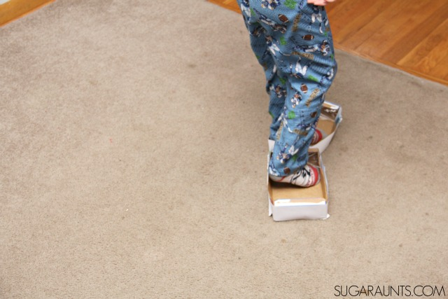 Indoor ice skates with cardboard boxes add proprioception and vestibular sensory play.