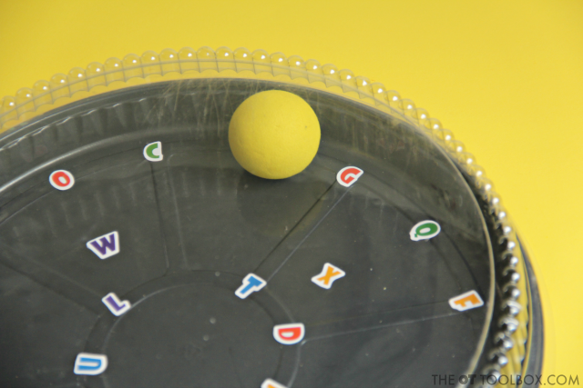 Kids can use a recycled cake pan to work on hand-eye coordination and visual motor skills needed for reading, writing, and many other functional skills in occupational therapy activities.
